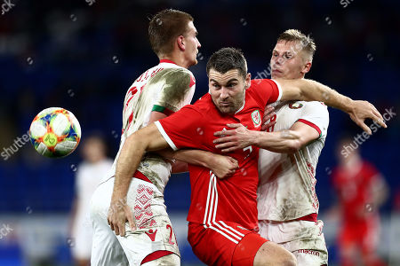 Sam Vokes of Wales is held back by Kirill Pechenim and Nikolai Zolotov of Belarus.