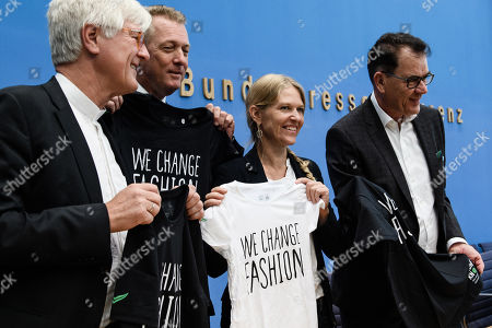 """(L-R) Council Chairman of the Evangelical Church in Germany (EKD) Heinrich Bedford-Strohm, the CEO of coffee retailer Tchibo Thomas Linemayr, CEO of the outdoor brand VAUDE Antje von Dewitz and German Minister of Economic Cooperation and Development Gerd Mueller pose with t-shirts reading 'We change Fashion"""" during the beginning of a press conference on the presentation of the Green Button (Gruener Knopf) textile label in Berlin, Germany, 09 September 2019. With the certified Green Button textile label, German Minister of Economic Cooperation and Development Gerd Mueller wants to mark sustainable clothing."""