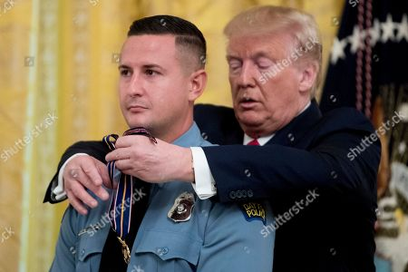 Donald Trump, Jeremy Campbell. President Donald Trump presents the Medal of Valor to Dayton Police Officer Jeremy Campbell, one of the six police officers who helped stop a mass shooter in Dayton, Ohio, during a ceremony in the East Room of the White House in Washington