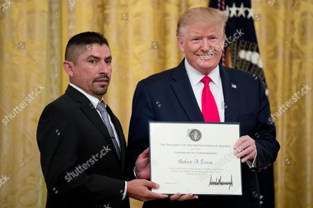 Stock Photo of Donald Trump, Robert Evans. President Donald Trump presents a Certificate of Commendation to Robert Evans, one of five civilians celebrated for their heroism during the mass shooting in El Paso, Texas, during a ceremony in the East Room of the White House in Washington