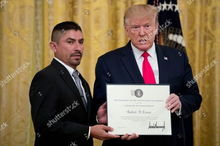 Stock Picture of Donald Trump, Robert Evans. President Donald Trump presents a Certificate of Commendation to Robert Evans, one of five civilians celebrated for their heroism during the mass shooting in El Paso, Texas, during a ceremony in the East Room of the White House in Washington