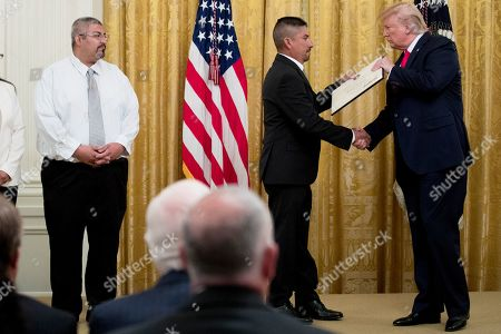 Donald Trump, Robert Evans. President Donald Trump presents a Certificate of Commendation to Robert Evans, second from right, one of five civilians celebrated for their heroism during a mass shooting in El Paso, Texas, at a ceremony in the East Room of the White House in Washington