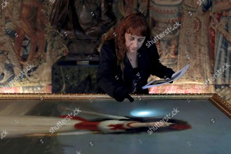 Stock Image of A curator takes a close look at the artwork of the Spanish painter Goya, 'Duchess of Alba' (lit. La duquesa se Alba) in the Palace of Liria in Madrid, Spain, 09 September 2019. This and other artworks made by national painters, have returned to the Palace of Liria after being borrowed to the Thyssen Museum for the exposition 'Balenciaga and Spanish painting'.