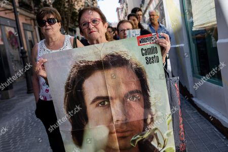 A woman holds a picture of late Spanish singer and songwriter Camilo Sesto as she queues to see his coffin in Madrid, . Spanish singer and songwriter Camilo Sesto, a popular star in the 1970s and 1980s, died on Sunday Sept. 8, of heart failure. Sesto, whose real name was Camilo Blanes Cortes, sold more than 100 million records worldwide over his 40-year career