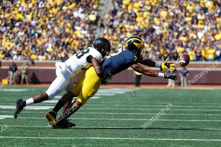 Michigan wide receiver Tarik Black (7) tries to catch a pass while being defended by Army defensive back Jabari Moore (28) in the first half of an NCAA college football game in Ann Arbor, Mich