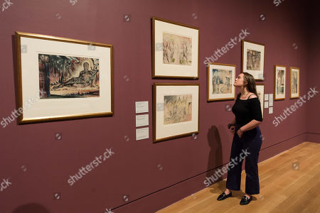 "A gallery staff member views late works by British artist William Blake (1757-1827), including illustration for The Divine Comedy by Dante Alighieri (Inferno XIV, 46-72) ""Capaneus the Blasphemer""  (1824-1827) (1st left) during a photocall to promote the upcoming exhibition at the Tate Britain in London."