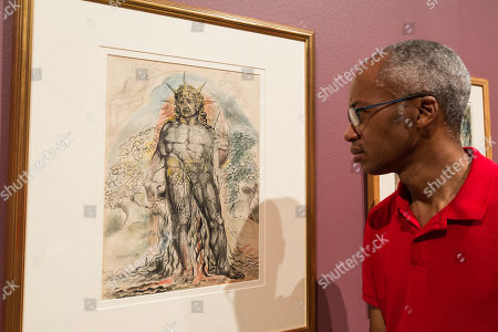 "A gallery staff member views ""The Symbolic Figure of the Course of Human History described by Virgil"" (1824-1827) by British artist William Blake (1757-1827) during a photocall to promote the upcoming exhibition at the Tate Britain in London."
