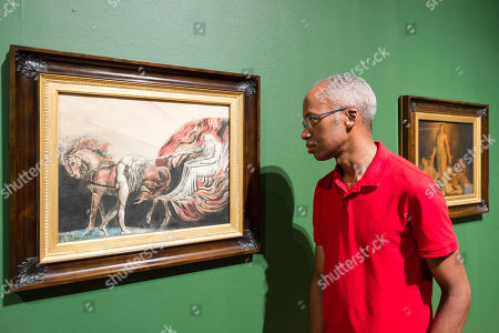 """A gallery staff member views """"God Judging Adam"""", 1795, by British artist William Blake (1757-1827) during a photocall to promote the upcoming exhibition at the Tate Britain in London, England."""