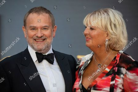Hugh Bonneville, Lulu Evans. Actor Hugh Bonneville, left and wife Lulu Evans pose for photographers upon arrival at the world premiere of the film 'Downton Abbey' in London