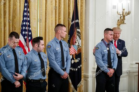 US President Donald Trump (R) awards Dayton Police Officer Jeremy Campbell (2-R) the Medal of Valor during a ceremony in the East Room of the White House in Washington, DC, USA, 09 September 2019. The awards were presented to Dayton Police Officers and El Paso citizens following their actions during the mass shootings in their respective communities.