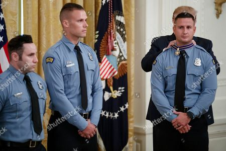 US President Donald Trump (R) awards Dayton Police Officer Jeremy Campbell the Medal of Valor during a ceremony in the East Room of the White House in Washington, DC, USA, 09 September 2019. The awards were presented to Dayton Police Officers and El Paso citizens following their actions during the mass shootings in their respective communities.