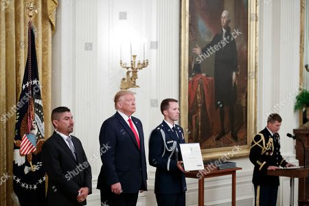 US President Donald Trump (2-L) presents Robert Evans (L) with a Heroic Commendation during a ceremony in the East Room of the White House in Washington, DC, USA, 09 September 2019. The awards were presented to Dayton Police Officers and El Paso citizens following their actions during the mass shootings in their respective communities.