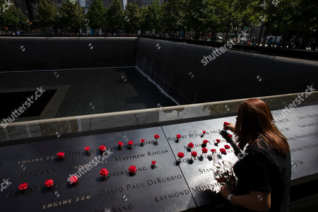Norma Molina, of San Antonio, Texas, leaves flowers by the names of firefighters from Engine 33 at the September 11 Memorial, in New York. Her boyfriend Robert Edward Evans, a member of Engine 33, was killed in the north tower of the World Trade Center on Sept. 11, 2001