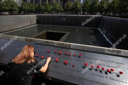 Stock Picture of Norma Molina, of San Antonio, Texas, leaves flowers by the names of firefighters from Engine 33 at the September 11 Memorial, in New York. Her boyfriend Robert Edward Evans, a member of Engine 33, was killed in the north tower of the World Trade Center on Sept. 11, 2001