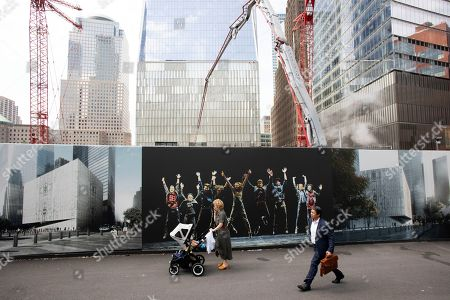 People walk by murals promoting the future site of the Ronald O. Perelman Performing Arts Center as cranes work over the site at the World Trade Center, in New York. The arts building is one of the final pieces to be completed as part of the reconstruction of the World Trade Center. Wednesday marks the 18th anniversary of the attacks of Sept. 11, 2001