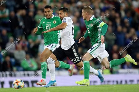 Germany's Emre Can runs with the ball between Northern Ireland's Josh Magennis, left, and Steven Davis during the Euro 2020 group C qualifying soccer match between Northern Ireland and Germany at Windsor Park, Belfast, Northern Ireland