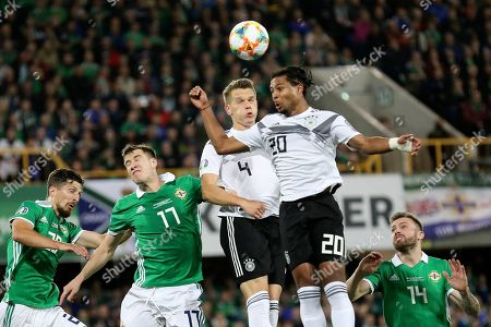 Germany's Matthias Ginter and Germany's Serge Gnabry, 2nf right, jump for the ball between Northern Ireland's Craig Cathcart, Paddy McNair and Stuart Dallas, from left, during the Euro 2020 group C qualifying soccer match between Northern Ireland and Germany at Windsor Park, Belfast, Northern Ireland
