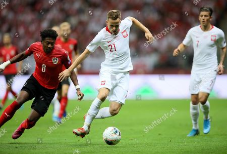 Tomasz Kedziora (C) of Poland and David Alaba (L) of Austria in action during the UEFA EURO 2020 group G qualifying soccer match between Poland and Austria at PGE National stadium in Warsaw, Poland, 09 September 2019.