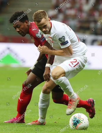 Tomasz Kedziora, David Alaba. Poland's Tomasz Kedziora, right, fights for the ball with the Austria's David Alaba during a Euro 2020 group G qualifying soccer match between Poland and Austria at PGE National stadium in Warsaw, Poland
