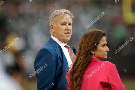 Denver Broncos President John Elway stands on the sidelines with ESPN reporter Dianna Russini before the start of an NFL football game against the Oakland Raiders, in Oakland, Calif
