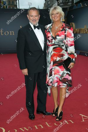 Stock Image of Hugh Bonneville, Lulu Evans. Hugh Bonneville, left and wife Lulu Evans pose for photographers upon arrival at the World premiere of the film 'Downton Abbey' in central London