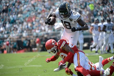 Jacksonville Jaguars wide receiver Chris Conley (18) is upended by Kansas City Chiefs cornerback Kendall Fuller (29) after catching a pass during the first half of an NFL football game, in Jacksonville, Fla