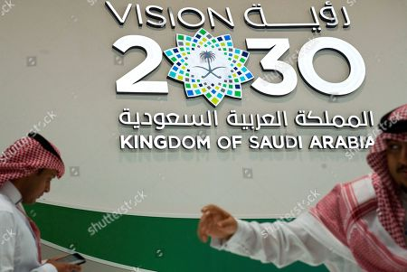 """Saudi men walk past a """"Vision 2030"""" display at a stand about Saudi Arabia during the World Energy Congress in Abu Dhabi, United Arab Emirates, . Amin Nasser, the chairman and CEO of the state-run oil giant Saudi Aramco, told journalists Tuesday a planned initial public offering of a sliver of the company's worth would happen """"very soon."""" """"Vision 2030"""" is an ambitious plan by Saudi Arabia's Crown Prince Mohammed bin Salman that includes the IPO of a small part of Saudi Aramco to help fund its efforts"""