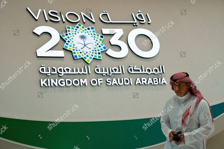 """A Saudi man walks past a """"Vision 2030"""" display at a stand about Saudi Arabia during the World Energy Congress in Abu Dhabi, United Arab Emirates, . Amin Nasser, the chairman and CEO of the state-run oil giant Saudi Aramco, told journalists Tuesday a planned initial public offering of a sliver of the company's worth would happen """"very soon."""" """"Vision 2030"""" is an ambitious plan by Saudi Arabia's Crown Prince Mohammed bin Salman that includes the IPO of a small part of Saudi Aramco to help fund its efforts"""