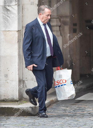 Conservative MP Liam Fox carries a Tesco shopping bag as he arrives at Parliament.