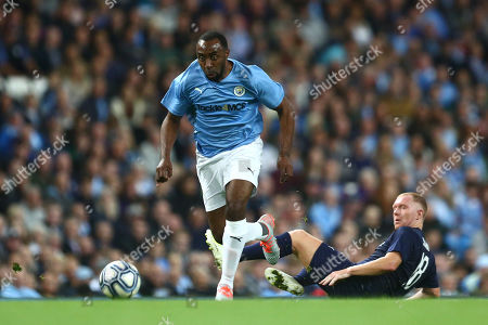 Darius Vassell of Manchester City Legends escapes a tackle from Paul Scholes of Premier League All-Stars