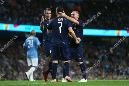 Robbie Keane of Premier League All-Stars celebrates scoring his sides first goal with Robin van Persie and Paul Scholes