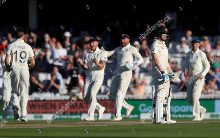 Steve Smith of Australia (2nd R) pauses before walking, after he is out LBW to England's Chris Woakes (L) for 80 runs