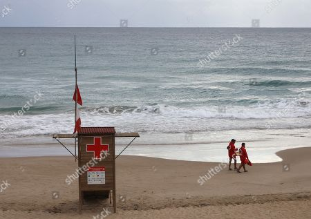 Two life guards walk along Cala dels Capellans beach in Tarragona, Spain, 10 September 2019. Strong rainfalls are expected in Catalonia during the day.