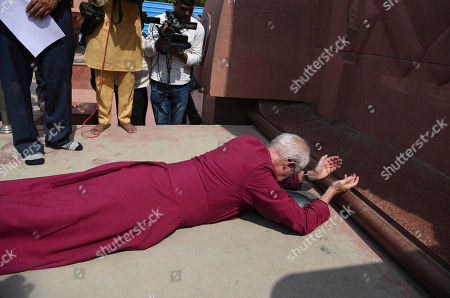 The Archbishop of Canterbury Rev. Justin Welby, prostrates as he pays respect at the Jallianwala Bagh memorial in Amritsar, India, . More than 300 Indians attending a peaceful rally calling for independence were killed during a massacre by British colonial troops at this spot 100 years ago