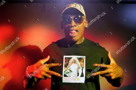 """Former basketball star Dennis Rodman poses wearing a T-shirt depicting himself in a wedding dress at a 1996 book promo event, in Los Angeles. After a career of spectacular highs and very public lows, Dennis Rodman keeps finding new ways to surprise. The former NBA star, featured in a new ESPN documentary, weighs in on his personal brand, bisexual athletes, North Korea and Trump. Rodman's spectacular personal highs and very public lows are the subject of the new ESPN """"30 For 30"""" documentary """"Dennis Rodman: For Better or Worse"""