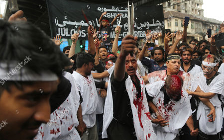 Indian Shiite Muslims flagellate themselves during a procession to mark Ashoura in Mumbai, .Ashoura falls on the 10th day of Muharram, the first month of the Islamic calendar, when Shiites mark the death of Hussein, the grandson of the Prophet Muhammad, at the Battle of Karbala in present-day Iraq in the 7th century