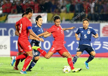 Myanmar's Zaw Lin, second right, vies for the ball with Japan's Yuto Nagatomo, right, during the World Cup 2022 Group F qualifying soccer match at Thuwunna stadium, in Yangon, Myanmar
