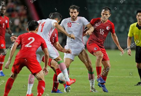 Vahid Amiri, Karim Ansarifard. Iran's Vahid Amiri, second left, and Karim Ansarifard, center, fight for a ball during the World Cup 2022 Group C qualifying soccer match between Hong Kong and Iran in Hong Kong