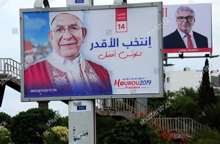 Electoral posters for presidential candidates Abdelfattah Mourou, of the moderate Islamist party Ennahdha, and Defense Minister Abdelkarim Zbidi, right, are pictured in Tunis. Tunisia's 26 presidential candidates launched their campaigns last week in a political climate marked by uncertainty, money laundering allegations and worries about violent extremism