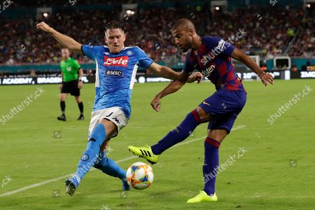Barcelona midfielder Rafinha, right, kicks and Napoli midfielder Piotr Zielinski defends during the second half of a LaLiga-Serie A Cup soccer match, in Miami Gardens, Fla. Barcelona won 2-1