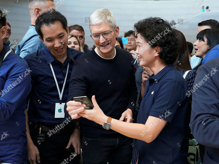 Apple CEO Tim Cook, center, looks at the the new iPhone 11 Pro Max, during an event to announce new products, in Cupertino, Calif
