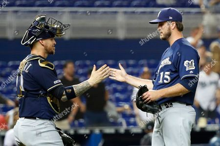 Yasmani Grandal, Drew Pomeranz. Milwaukee Brewers closing pitcher Drew Pomeranz (15) and catcher Yasmani Grandal (10) congratulate each other after the Brewers defeated the Miami Marlins 4-3 during a baseball game, in Miami