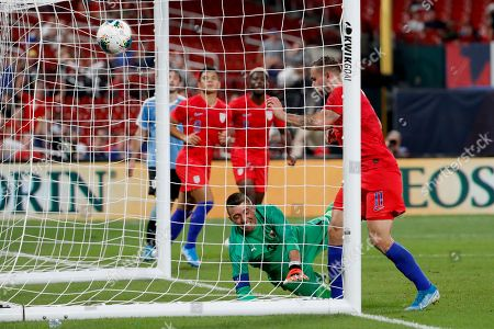United States' Jordan Morris (11) scores past Uruguay goalkeeper Fernando Muslera during the second half of a friendly soccer match, in St. Louis. The game ended in a 1-1 tie