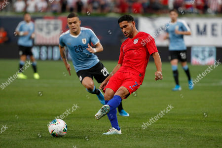 United States' Cristian Roldan (7) passes as Uruguay's Jonathan Rodriguez (20) watches during the first half of a friendly soccer match, in St. Louis