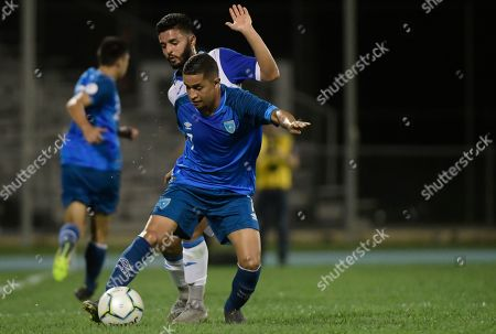 Guatemala's Marvin Ceballos (blue) and Puerto Rico's Jose Calderon (white) vie for the ball during the first half of the CONCACAF Nations League qualifying soccer match, in Mayaguez, Puerto Rico