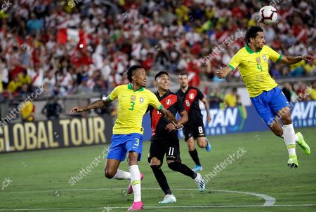 Marquinhos, Raul Ruidiaz, Eden Militao. Brazil's Marquinhos, right, clears the ball with a header in front of Peru's Raul Ruidiaz (11) and Brazil's Eder Militao during the first half of an international friendly soccer match, in Los Angeles