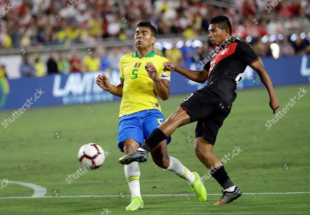 Stock Photo of Edison Flores, Casemiro. Peru's Edison Flores, right, takes a shot on goal as Brazil's Casemiro defends during the first half of an international friendly soccer match, in Los Angeles