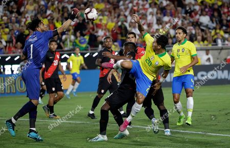 Pedro Gallese, Roberto Firmino. Peru goalkeeper Pedro Gallese, left, punches the ball next to Brazil's Roberto Firmino (20) during the second half of an international friendly soccer match, in Los Angeles
