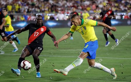 Richarlison, Luis Advincula. Brazil's Richarlison, left, shoots pat Peru's Luis Advincula during the second half of an international friendly soccer match, in Los Angeles