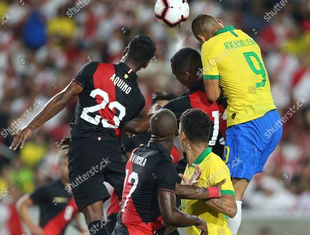 Pedro Aquino (L) of Peru in action against Richarlison (R) of Brazil during a friendly soccer match between Brazil and Peru at the Los Angeles Memorial Coliseum in Los Angeles, California, USA, 10 September 2019.